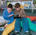 Photo of two children listening to audiobooks on the digital talking book machine