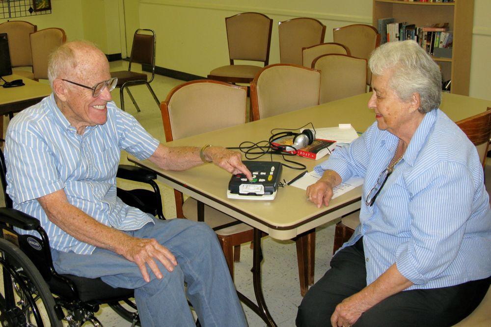 Betty Hall, a user of TBBC's audiobook service, explains the operation of the audio player to Larry Mansier, chairman of the Senior Advisory Board.