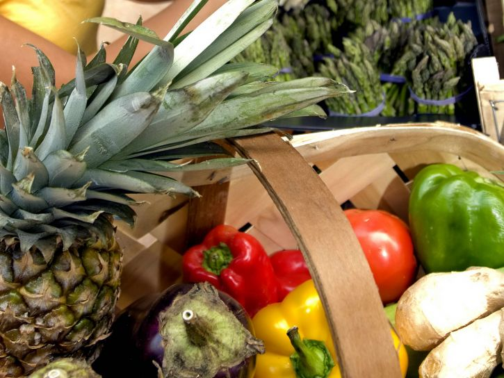 Photo of fruit and vegetables at a grocery store, including a pineapple, red pepper, eggplant, yellow pepper, green pepper, tomato, asparagus